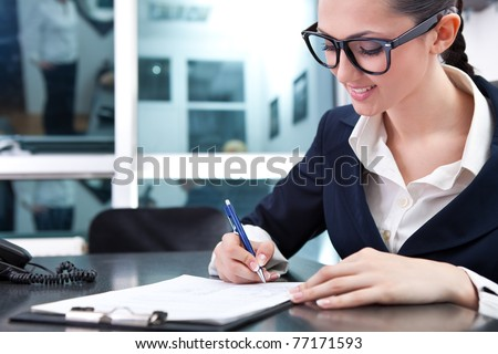 smiling businesswoman signing a contract in office - stock photo