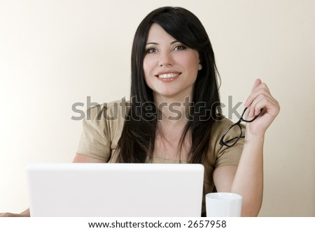Smiling businesswoman sitting at computer.