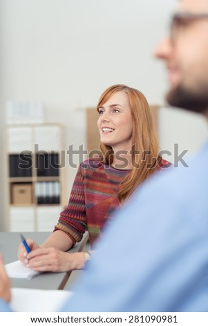 Smiling businesswoman sitting at her desk with a male colleague watching something in the office, view over his shoulder - stock photo