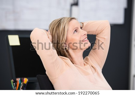 Smiling businesswoman sitting daydreaming as she relaxes at the offices sitting back in her chair with her hands clasped behind her head - stock photo