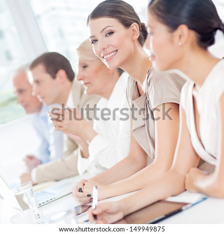 Smiling businesswoman sitting in a meeting with her colleagues. - stock photo
