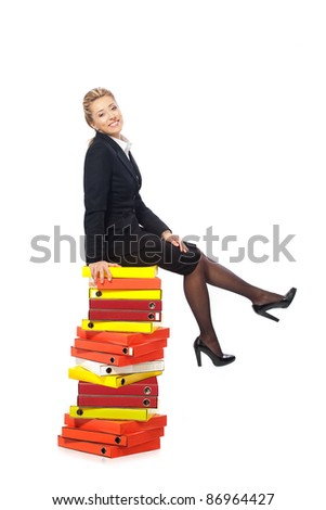Smiling businesswoman sitting on a stack of folders - stock photo
