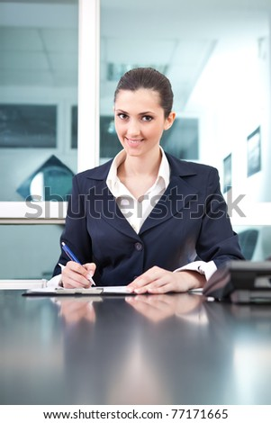 smiling businesswoman sitting on desk in office - stock photo
