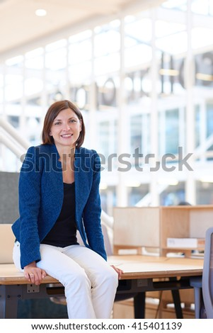 Smiling businesswoman sitting on her desk in modern office - stock photo