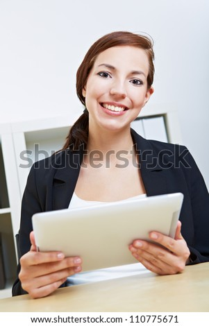 Smiling businesswoman sitting with her tablet pc in an office - stock photo