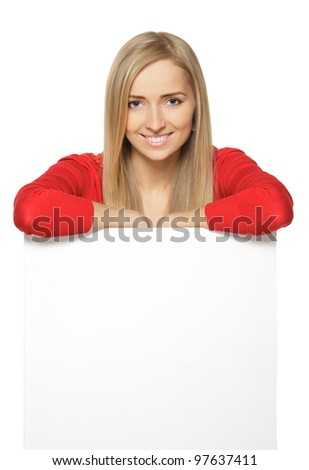 Smiling businesswoman standing behind and leaning on a white blank billboard / placard, over white background - stock photo