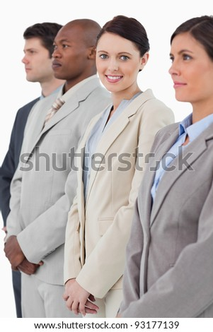 Smiling businesswoman standing between her associates against a white background