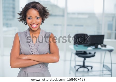 Smiling businesswoman standing in office and crossing her arms while looking at camera - stock photo
