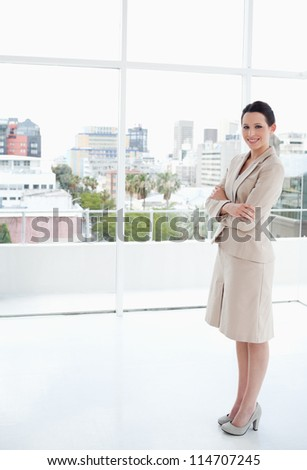 Smiling businesswoman standing upright in front of the bright window - stock photo