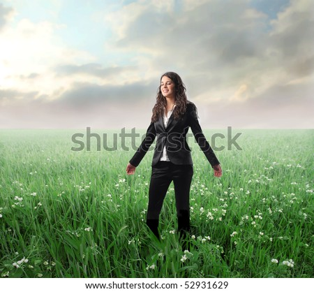 Smiling businesswoman standing with open arms on a green meadow - stock photo