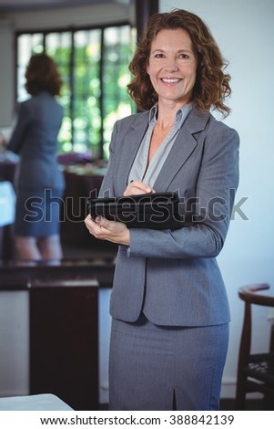 Smiling businesswoman taking notes in a restaurant