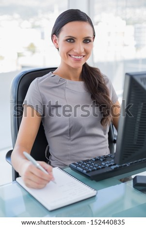 Smiling businesswoman taking notes in her office