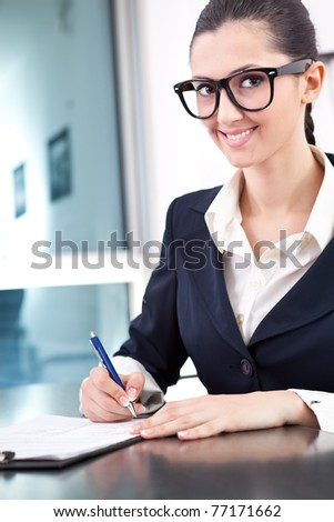 smiling businesswoman taking notes in office - stock photo