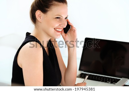 Smiling businesswoman talking on mobile phone in a office - stock photo