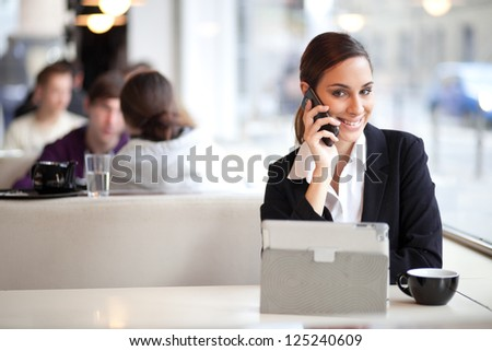 Smiling businesswoman talking on the phone and using tablet computer in a coffee shop - stock photo