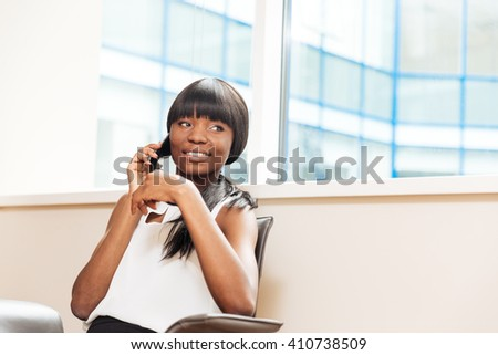 Smiling businesswoman talking on the phone in office and looking away - stock photo