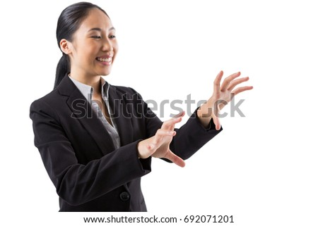 Smiling businesswoman touching the invisible screen against white background