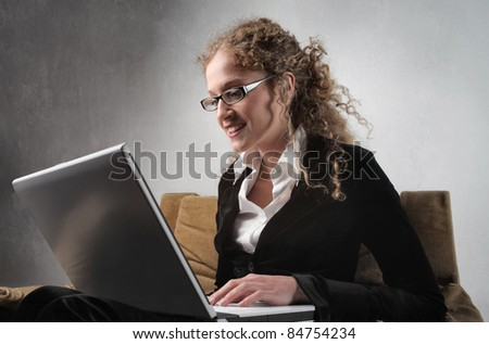 Smiling businesswoman using a laptop - stock photo