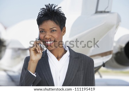 Smiling businesswoman using cellphone with airplane in background - stock photo