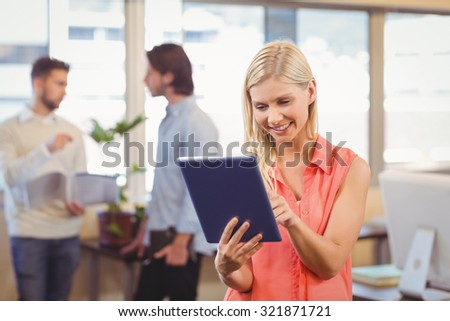 Smiling businesswoman using digital PC with male colleagues standing in background in creative office