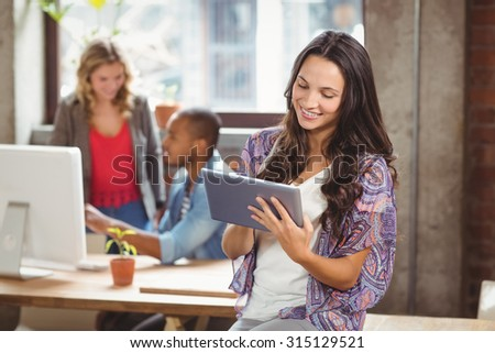 Smiling businesswoman using digital tablet in creative office - stock photo