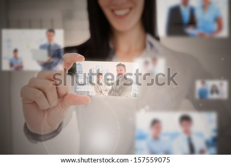 Smiling businesswoman using futuristic interface showing business people - stock photo