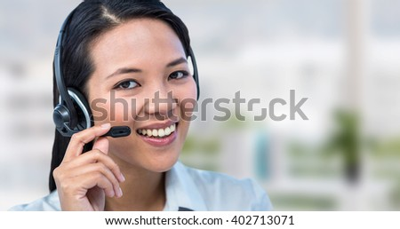 Smiling businesswoman using headset against office