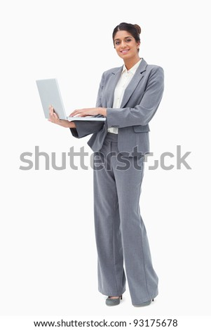 Smiling businesswoman using laptop white standing against a white background