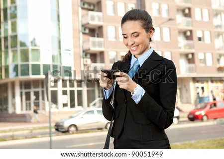 smiling businesswoman using  smart phone, outdoor - stock photo