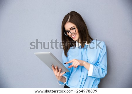 Smiling businesswoman using tablet computer over gray background. Wearing in blue shirt and glasses - stock photo