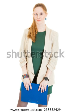 smiling businesswoman wearing a green dress and jacket standing with files - stock photo