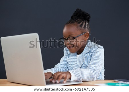 Smiling businesswoman wearing eyeglasses using laptop while sitting at desk in office