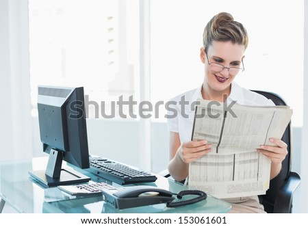 Smiling businesswoman wearing glasses reading newspaper in her office - stock photo