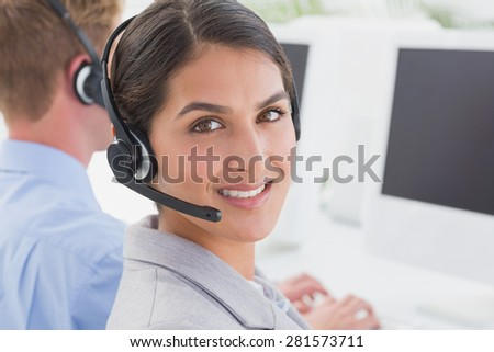 Smiling businesswoman wearing headset in call center
