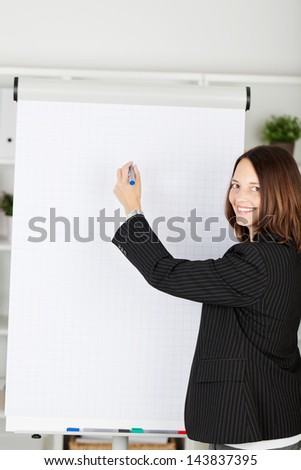 Smiling businesswoman with a blank flipchart standing looking at the camera with her hand raised holding a marker pen as though writing up a presentation - stock photo