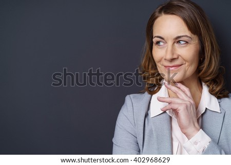 Smiling businesswoman with a thoughtful expression standing with her hand to her chin looking to the side to blank copy space on a dark background - stock photo