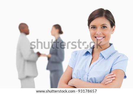 Smiling businesswoman with arms crossed and colleagues behind her against a white background