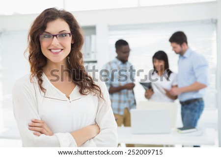 Smiling businesswoman with arms crossed in front of her colleagues - stock photo