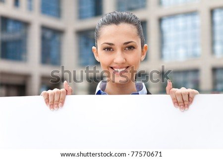smiling businesswoman with banner, outdoor - stock photo