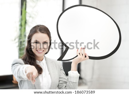 smiling businesswoman with blank text bubble pointing at you - stock photo