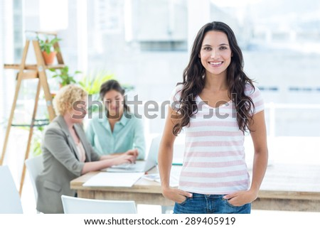 Smiling businesswoman with colleagues in an office - stock photo