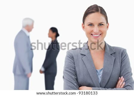 Smiling businesswoman with folded arms and colleagues behind her against a white background