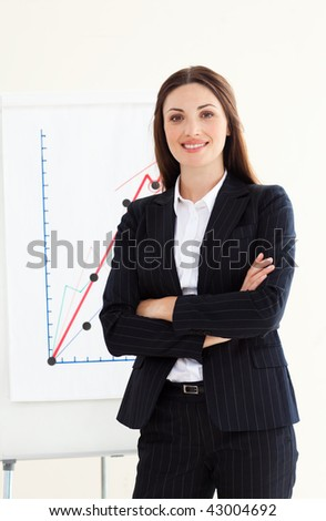Smiling businesswoman with folded arms in front of a board - stock photo