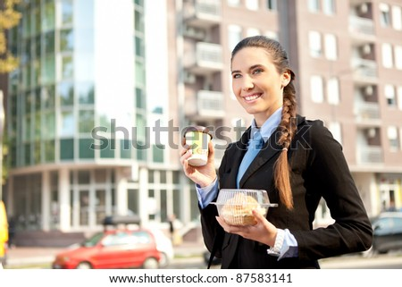 smiling businesswoman with her breakfast, outdoor - stock photo