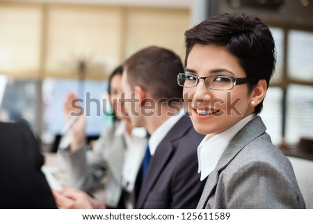 Smiling businesswoman with her colleagues in background - stock photo