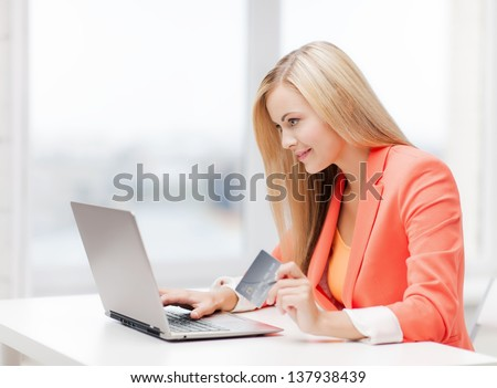 smiling businesswoman with laptop and credit card - stock photo