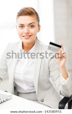smiling businesswoman with laptop showing credit card