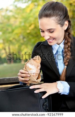 smiling businesswoman with pastry, breakfast break, outdoor - stock photo