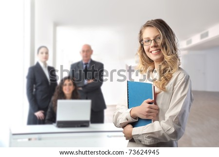 Smiling businesswoman with team on the background - stock photo
