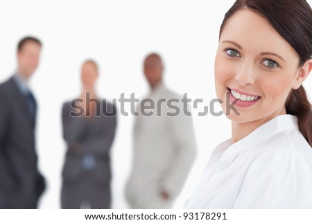 Smiling businesswoman with three colleagues behind her against a white background